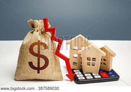 Dollar Money Bag With Down Arrow And Houses On Calculator. Falling Real Estate Market, Low Prices An