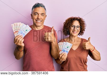Beautiful middle age couple holding colombian pesos banknotes smiling happy and positive, thumb up doing excellent and approval sign