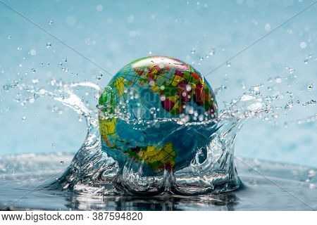 Planet Earth In The Form Of A Globe In Clear Water With Splashes. Concept Of Eco Friendly Behavior,