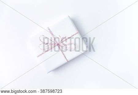 White gift box with pink ribbon on white background. Flat lay. Copy space