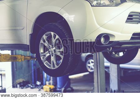 Car On A Lift In A Car Repair Station. Lifted Chassis Car For Repairing Under The Car In Garage Shop