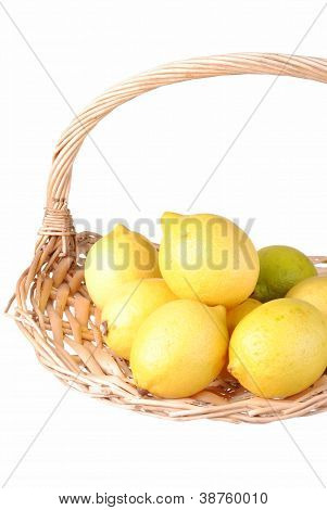organic lemons in a straw basket isolated on white