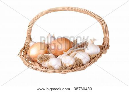 Garlic and onions in a straw basket isolated on white