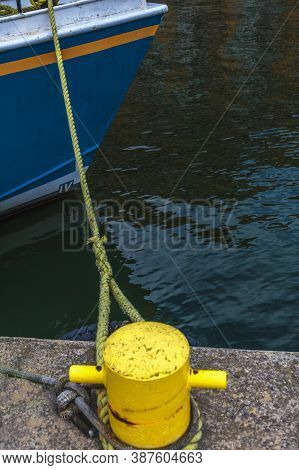 Boat Anchored With Mooring Rope Tied To A Bollard. Vertical Shot