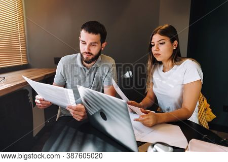A Young Couple Manages Finances By Looking Through Their Bank Accounts In The Living Room At Desk Us