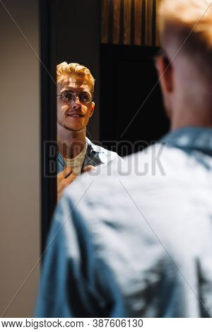 Young Caucasian Man In Glasses Looks At Himself In The Mirror And Straightens His Shirt. High Qualit