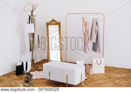 Rack With Stylish Womens Clothes, Grey Pouf And Mirror Indoors. Interior Design. High Quality Photo