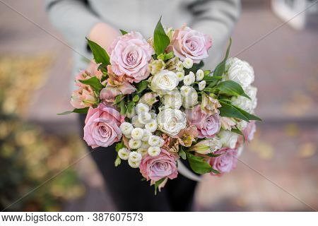 Florist Shop In Daylight. A Woman Holds A Beautiful Bouquet Of Flowers. Florist With Her Work. Styli
