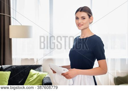 Chambermaid In Apron Holding Clean Towel And Looking At Camera In Hotel Room