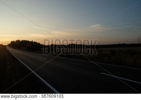 Direct Empty Suburban Road With New Road Marking Runs Far To The Horizon In The Sunset In The Evenin