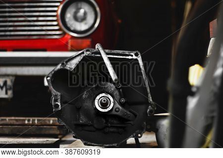 Car Gearbox. Disassembled Gearbox Against The Background Of A Red Car. Car Repair