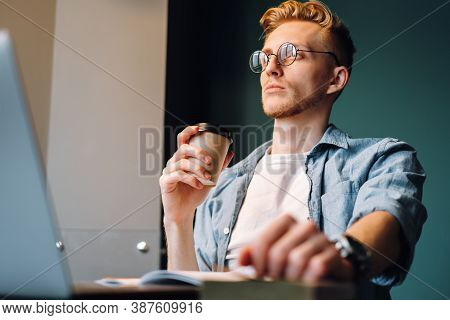 Caucasian Man College Student In Glasses Drinking Coffee While Studying With Books And Laptop Distan