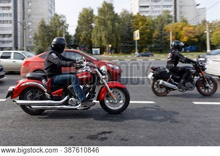 Ulyanovsk, Russia - September 26, 2020. Two Motorcyclists Ride A Motorcycle Among Cars Along A City