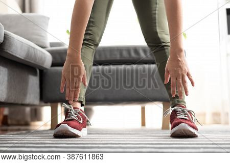 Close Up Hand Woman Touching Her Toes Stretches. Standing Forward Bend Yoga Pose Stretch At Home.