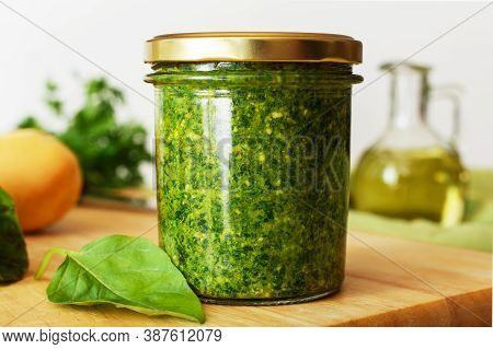 Homemade Pesto Sauce In A Glass Jar With Basil, Ingredients And Baguette On White Table In The Kitch