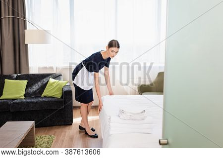 Chambermaid In Making Bed Near Towels In Hotel Room