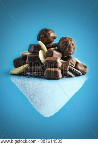 A Pile Of Delicious Chocolates And Its Reflection In The Form Of A Mountain Of White Crystalline Sug