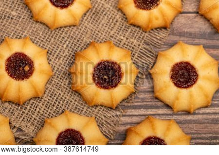 Homemade Pastry Cookies With Jam On A Background Of Homespun Fabric With A Rough Texture, Close-up,