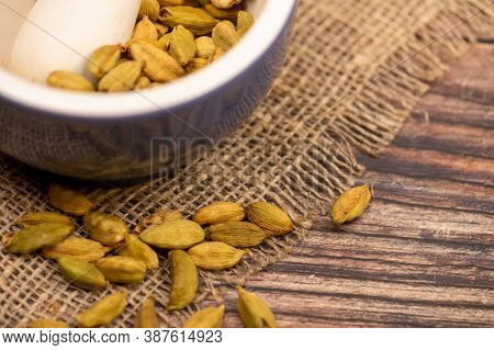 Cardamom In A Ceramic Mortar And Cardamom In A Loose Background Of Coarse Burlap, Close-up, Selectiv