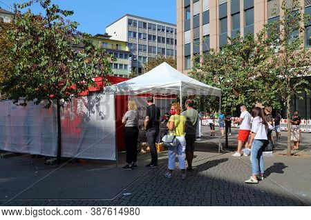 Dusseldorf, Germany - September 19, 2020: People Wait In Line For A Covid-19 (coronavirus) Temporary
