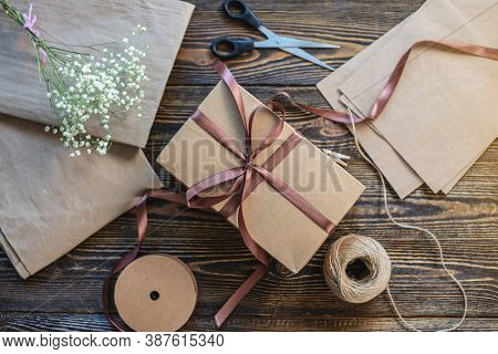 Craft Paper And Tools For Creating And Decorating Gift Packaging. There Is Cardboard, Brown Ribbons