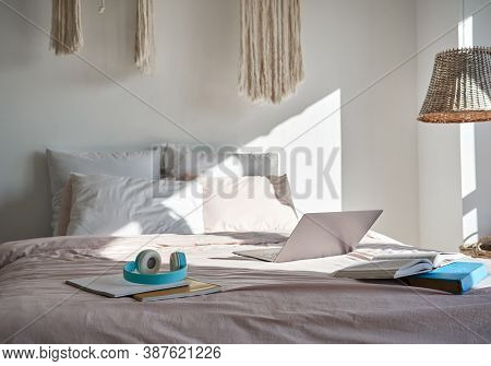 Modern Bedroom Interior With Laptop Computer, Headphones, Books On Cozy Bed In Sunny Room. Cosy Hygg