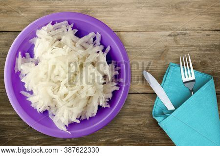 Daikon On Brown Wooden Background. Daikon On Purple Plate With Fork And Knife Top View