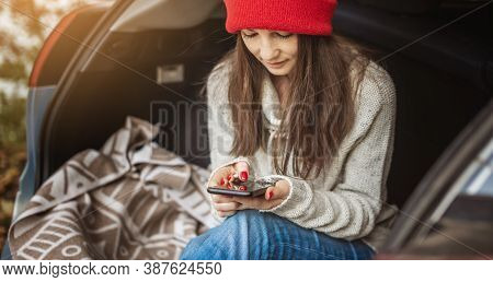 Woman In A Car Is Holding A Mobile Phone Gadget In The Trunk At A Picnic. Cozy Autumn Weekend Trip.
