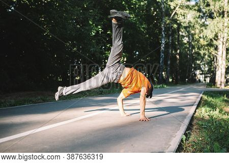 Cool Young Guy Breakdancer Dances On The Road In The Park In Summertime