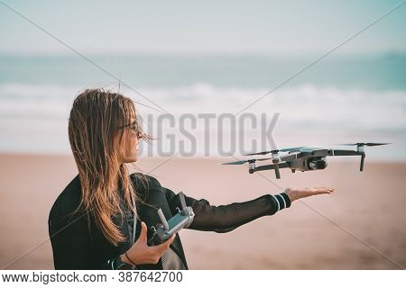 Young Modern Lady Pilot In Black Jacket Lands Drone On Her Hand With Remote Controller Near The Ocea