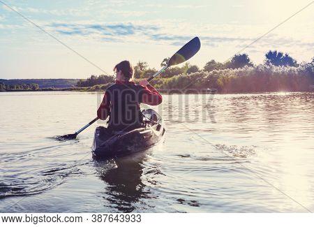Rear view of kayaker  paddle kayak in summer river