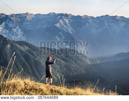 Young Active Man With Photographic Camera Taking Photo At Mountains Background