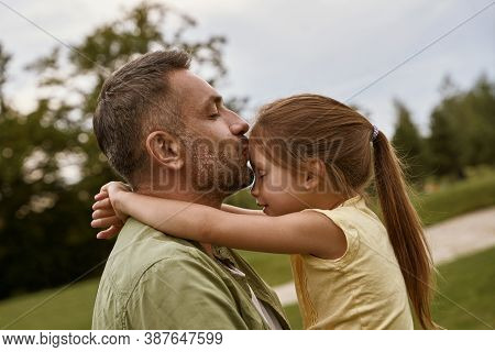 Young Loving Father Kissing His Cute Little Daughter In Forehead While Spending Time Together Outdoo