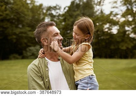Cute Little Girl Playing With Her Loving Father While Visiting Park On A Summer Day, Touching His Ch