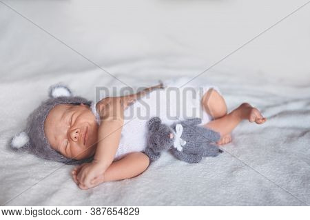 Cute Emotional Newborn Little Baby Boy Sleeping In Crib In A Knitted Suit With Toy. Baby Goods Packa