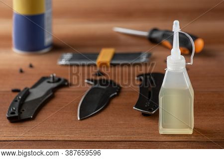 Bottle Of Household Oil, Parts Of A Disassembled Knife And Tools On Wooden Table