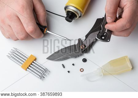 Man Repairing A Folding Knife On White Background