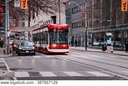 Toronto, Canada - 01 04 2020: A New Bombardier Made Streetcar And Cars Standing At Traffic Lights On