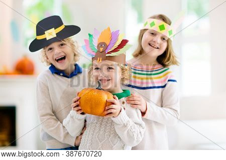 Child Celebrating Thanksgiving. Kid Holding Pumpkin In Paper Turkey Hat. Autumn Fun Crafts And Art.