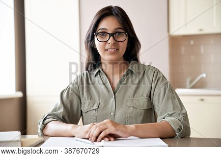 Smiling Young Indian Female Teacher Wearing Glasses Sitting At Table. Indian Woman School Tutor Or U
