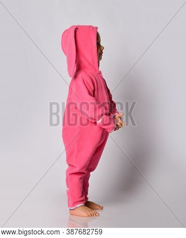 Small Barefoot Cute Blonde Baby Girl In Pink Warm Comfortable Jumpsuit With Hood And Bunny Ears Stan