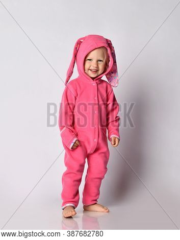 Laughing Barefooted Cute Blonde Baby Girl In Pink Warm Comfortable Jumpsuit Stands Looking At Camera
