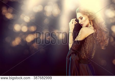 Portrait of an gorgeous woman  in evening dress on a dark background with golden magic lights. Evening fashion. Copy space.