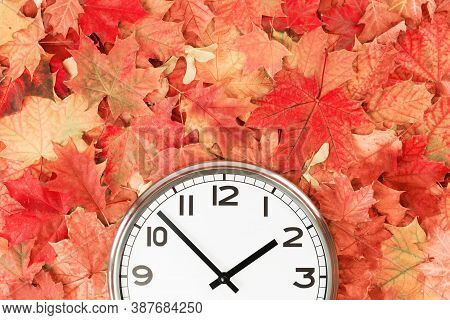 Plain Wall Clock In The Center Of Autumn Orange Red Leaves And Fall Foliage. Two Oclock. Copy Space,