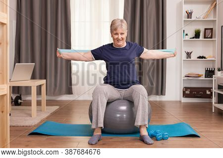 Senior Woman Working Out At Home With Fitness Bands To Solve Her Health Problems. Old Person Pension