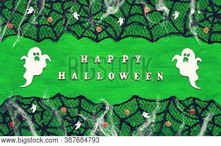 Halloween background. Inscription Happy Halloween and Halloween decorations on the bright green wooden background, Happy Halloween concept, happy Halloween card