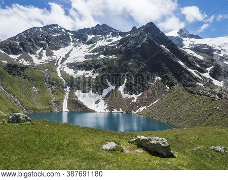 Beautiful Turquoise Blue Mountain Lake Grunausee In Alpine Landscape With Green Meadow And Snow-capp
