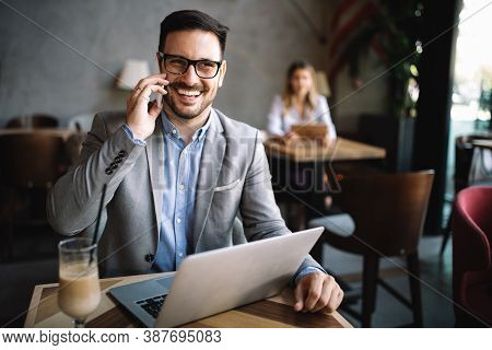 Handsome Business Man Receiving A Happy Message On His Cell Phone