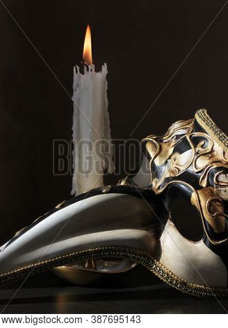 Retro Style Still Life With Beaked Venetian Carnival Plague Doctor Mask And Vintage Candlestick With