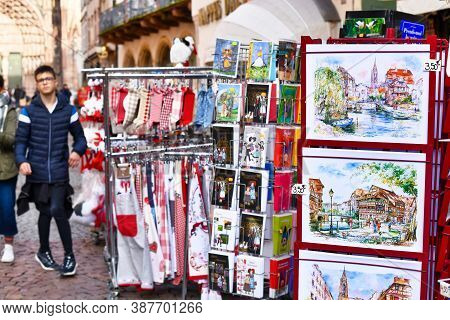 Strasbourg, France - February 2020: Racks With Souvenirs Like Paintings, Post Cards And Home Utensil